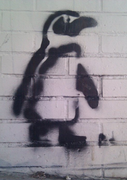 Graffiti Penguin on white brick outside of Illini Media in Champaign Illinois