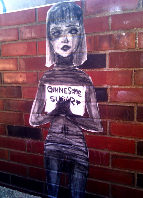 Full body of the Sugar Face Girl plastered onto brick at the University of Illinois Campus in front of the Undergraduate Library