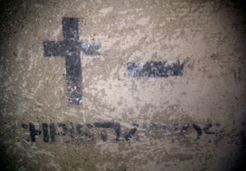 """Christ Menos"" text found under a cross and minus sign."