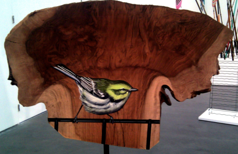 A bird sits on railing...painted on wood.