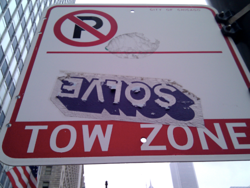 The word SOLVE upside down on a Tow Zone side in Chicago